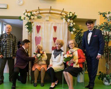 Śpiewacy Dariusz Wójcik i Jacek Szymański pozują do zdjęć z seniorami. Za nimi dekoracje z kwiatów.