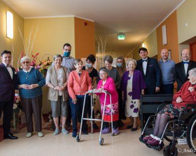 Zdjęcie grupowe. Muzycy, seniorzy, pracownicy uśmiechają się. W tle dekoracja z kwiatów.