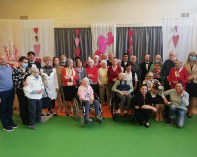 Zdjęcie grupowe. Muzycy, dyrektorka Agnieszka Cysewska, seniorzy, pracownicy uśmiechają się. W tle biało-różowa dekoracja.
