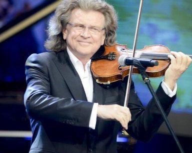 Piosenkarz Zbigniew Wodecki stoi przy mikrofonie i gra na skrzypcach. Jest ubrany w garnitur.