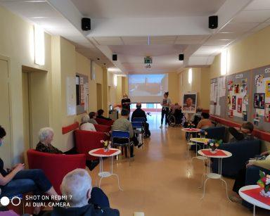 Seniorzy i pracownicy siedzą na korytarzu. Oglądają film wyświetlany na ekranie projektora.