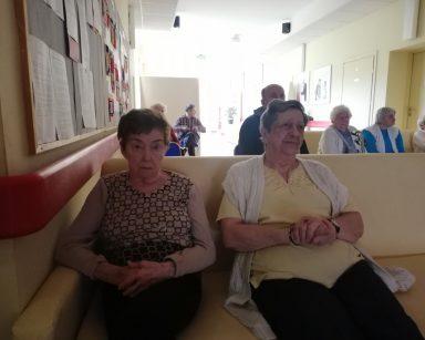 Korytarz. Seniorzy siedzą na krzesłach i kanapach. Oglądają film.