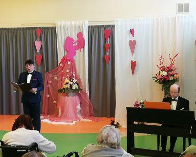 Tenor Jacek Szymański śpiewa, Michał Kaleta gra na pianinie. Za nimi dekoracja: serca, kwiaty, postać kobiety z noworodkiem.
