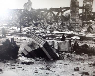 Czarno-białe zdjęcie powojennej Warszawy. Ruiny budowli i gruz.