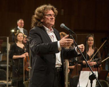 Przy mikrofonie stoi Zbigniew Wodecki. Jest ubrany w garnitur. W tle inni muzycy.