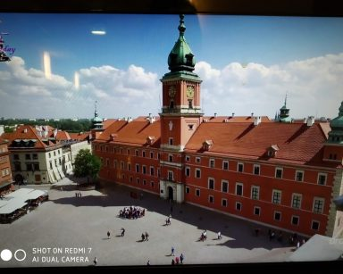 Zamek Królewski w Warszawie. Na placu przed nim spacerują ludzie.