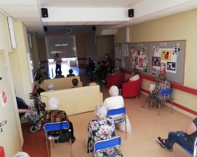 Pracownicy, mieszkańcy i uczestnicy dziennych zajęć siedzą na korytarzu. Przed nimi ekran, na nim napis: Zbigniew Wodecki.