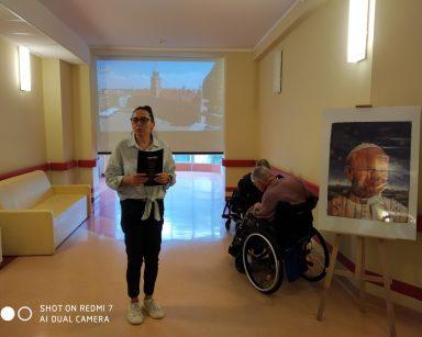 Terapeutka Magdalena Poraj-Górska stoi na tle ekranu projektora. Obok niej stelaż z plakatem papieża Jana Pawła II.