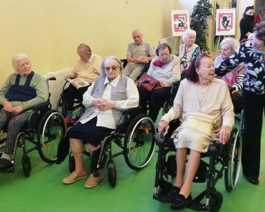 Seniorzy siedzą na sali. Czekają na początek koncertu.