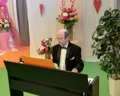 Muzyk Michał Kaleta gra na pianinie. W tle dekoracje: kwiaty, różowe serca.