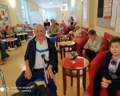 Uśmiechnięci seniorzy i pracownicy siedzą przy stolikach. Na blatach wazony z kolorowymi kwiatami.