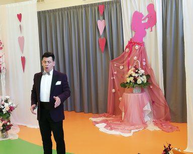 Artysta Dariusz Wójcik śpiewa. Za nim dekoracja: serca, kwiaty, różowa postać kobiety trzyma noworodka.