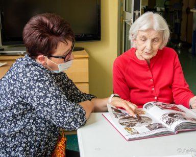 Koordynatorka wolontariatu Edyta Życzyńska i seniorka siedzą przy stoliku. Wspólnie oglądają album ze zdjęciami.