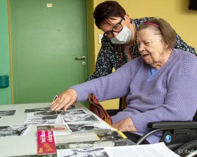 Seniorka siedzi przy stoliku. Nad nią pochyla się koordynatorka wolontariatu Edyta Życzyńska. Oglądają czarno-białe zdjęcia.