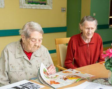 Dwie seniorki siedzą przy stole. Na blacie kolorowe magazyny, szklany wazon z różowymi kwiatami.