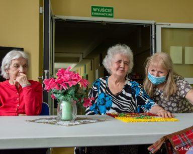 Przy stole dwie seniorki i terapeutka Ewa Rodziewicz. Na blacie wazon z kwiatami i obrazek z kolorowych kulek z bibuły.
