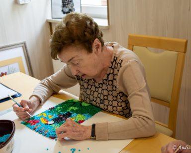 Seniorka wykańcza obrazek tukana. Nakleja kolorowe kulki z bibuły na arkusz papieru.