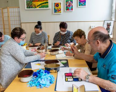 Seniorzy i pracownicy siedzą przy stołach nad pracami plastycznymi. Na ścianie oprawione kolorowe obrazki.