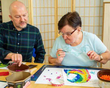 Kierownik Arkadiusz Wanat i seniorka przy stole. Seniorka pracuje nad portretem kobiety z kolorowych kulek z bibuły.