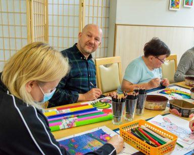 Seniorzy i pracownicy siedzą nad pracami plastycznymi. Na blacie mazaki, kredki, kolorowa bibuła, kulki, obrazki.