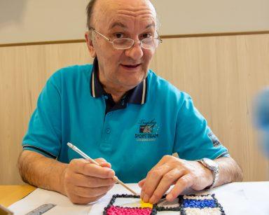 Senior uśmiecha się do zdjęcia. Pracuje nad fragmentem abstrakcyjnego obrazu z kolorowych kulek.