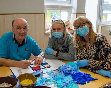 Dyrektorka Agnieszka Cysewska, kierowniczka Ilona Gajewska i senior uśmiechają się do zdjęcia. Na blacie pocięta bibuła.