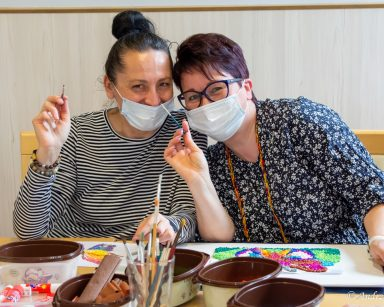 Terapeutka Magdalena Poraj-Górska i koordynatorka Edyta Życzyńska uśmiechają się. Przed nimi przybory plastyczne.
