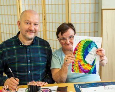 Kierownik Arkadiusz Wanat i seniorka uśmiechają się. Seniorka prezentuje częściowo wykonany portret kobiety.