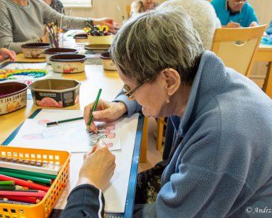 Seniorka z kredką w ręku nachyla się nad rysunkiem. W tle seniorzy i pracownicy zajmują się swoimi obrazami.
