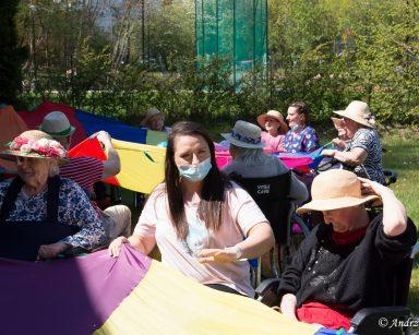 Na świeżym powietrzu siedzą pracownicy i seniorzy. Wspólnie bawią się trzymając tęczowe chusty.
