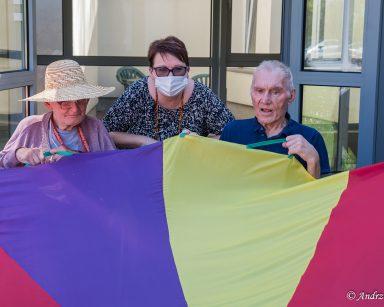 Na świeżym powietrzu siedzi koordynatorka wolontariatu Edyta Życzyńska i seniorzy. Wspólnie się bawią tęczową chustą.