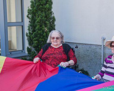 Na świeżym powietrzu siedzą dwie uśmiechnięte seniorki. Wspólnie bawią się trzymając fragment tęczowej chusty.