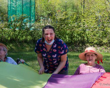 Ogród przed DPS. Roześmiana fizjoterapeutka Martyna Józefczyk i dwie seniorki. Bawią się trzymając tęczową chustę.