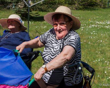 Na świeżym powietrzu siedzi roześmiana seniorka. W dłoniach trzyma fragment tęczowej chusty. W tle inni seniorzy, trawnik ze stokrotkami.