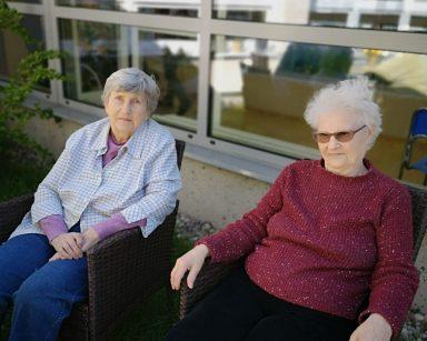 Słoneczny dzień, trawnik przed ogrodem zimowym. Dwie seniorki siedzą na krzesłach.