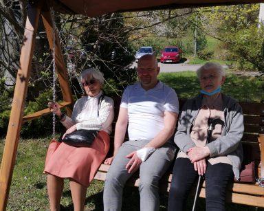 Słoneczny dzień, ogród przed DPS. Dwie seniorki i kierownik Arkadiusz Wanat siedzą razem na drewnianej huśtawce.