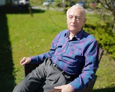 Słoneczny dzień, trawnik przed ogrodem zimowym. Senior siedzi na rattanowym fotelu.