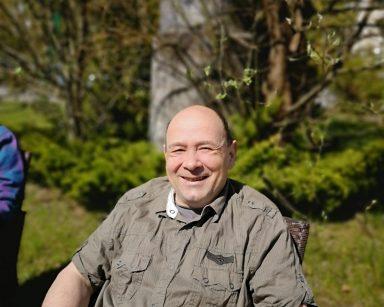 Słoneczny dzień, trawnik przed ogrodem zimowym. Uśmiechnięty senior siedzi na rattanowym fotelu.