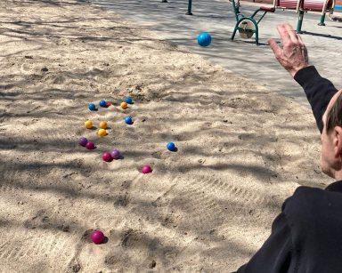 Na świeżym powietrzu senior rzuca niebieską piłkę do gry w boule. Przed nim na piasku kolorowe piłki do gry w boule.