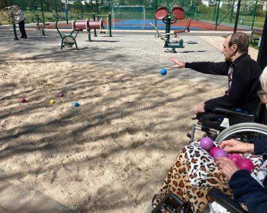 Na świeżym powietrzu senior rzuca niebieską piłkę do gry w boule. Drugi senior siedzi obok. Przed nimi na piasku kolorowe piłki.