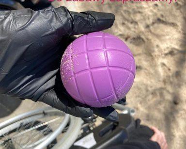 Ręka trzymająca filetową piłkę do gry w boule. U góry zdjęcia napis: Gramy w boule! W boule gramy! Do zabawy zapraszamy!