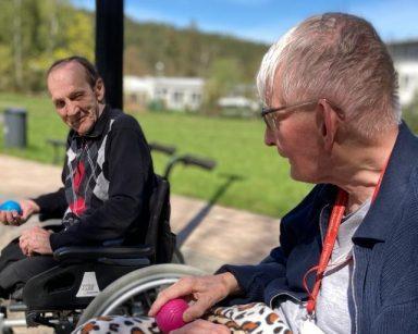 Słoneczny dzień, błękitne niebo. Na świeżym powietrzu dwóch seniorów gra razem w boule. W rękach trzymają piłki.
