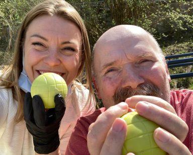 Słoneczny dzień. Uśmiechnięci senior i psycholożka Maria Skubich-Wiczling. W rękach trzymają żółte piłki do gry w boule.
