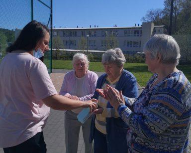 Boisko na świeżym powietrzu. Fizjoterapeutka Paulina Winczura dezynfekuje ręce seniorkom.