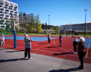 Boisko na świeżym powietrzu. Fizjoterapeutka Paulina Winczura ćwiczy z seniorami.