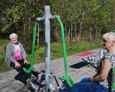Słoneczny dzień. Dwie seniorki ćwiczą na siłowni zewnętrznej.