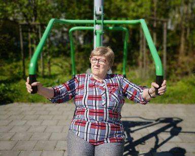 Seniorka ćwiczy na świeżym powietrzu.
