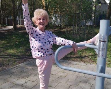 Seniorka gimnastykuje się na świeżym powietrzu. w tle drzewa, jasny budynek.