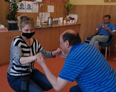 Terapeutka Beata Gadomska i senior tańczą trzymając się za ręce. Obok siedzi senior i patrzy na nich.