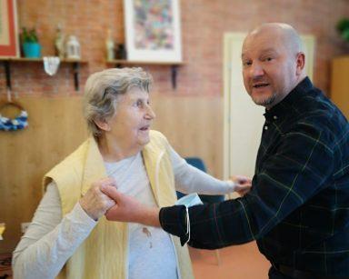 Jasna sala. Kierownik Arkadiusz Wanat i seniorka tańczą trzymając się za ręce.